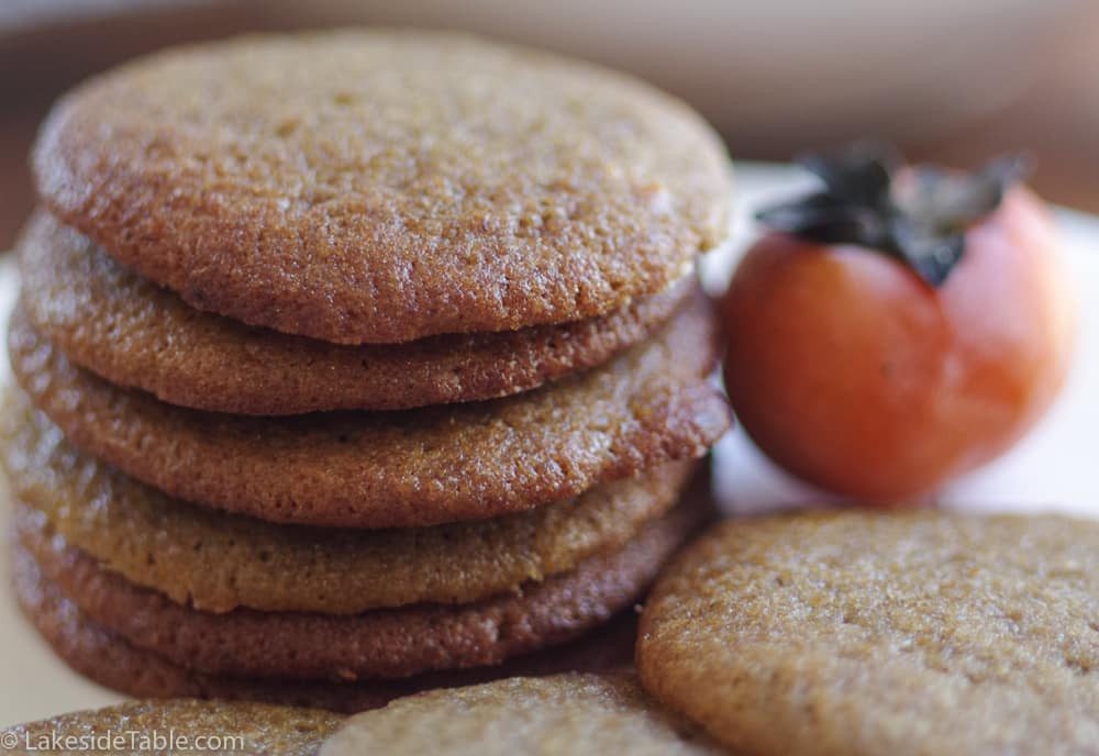 stack of thin and chewy persimmon cookies next to an American persimmon
