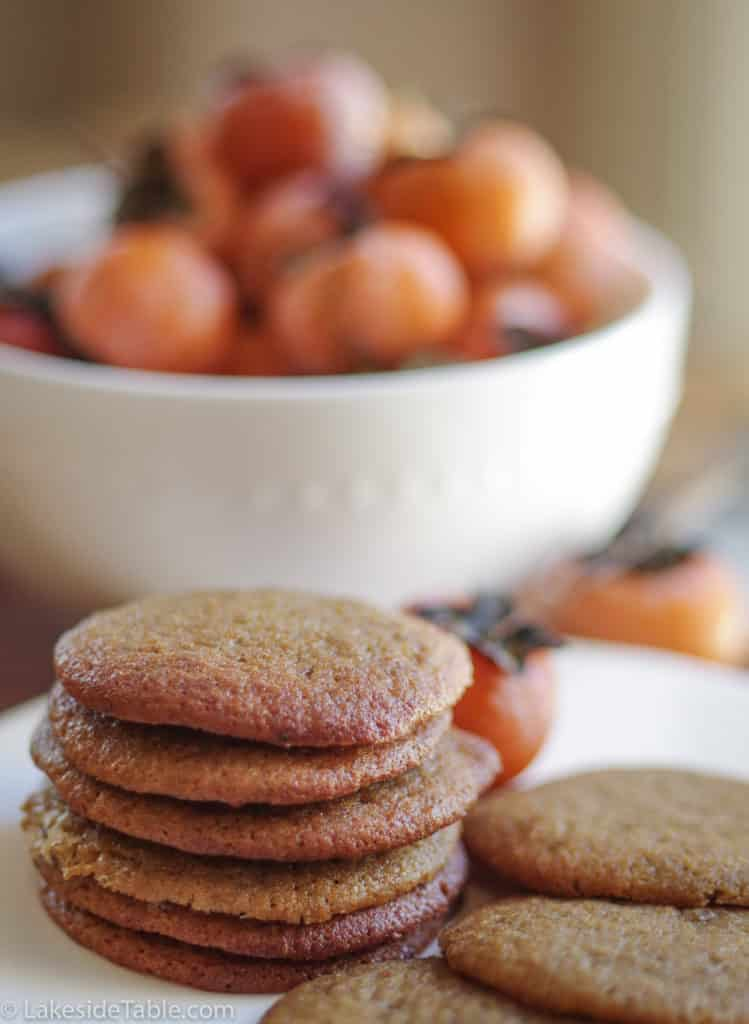 stack of persimmon cookies in front of a bowl of fresh persimmons