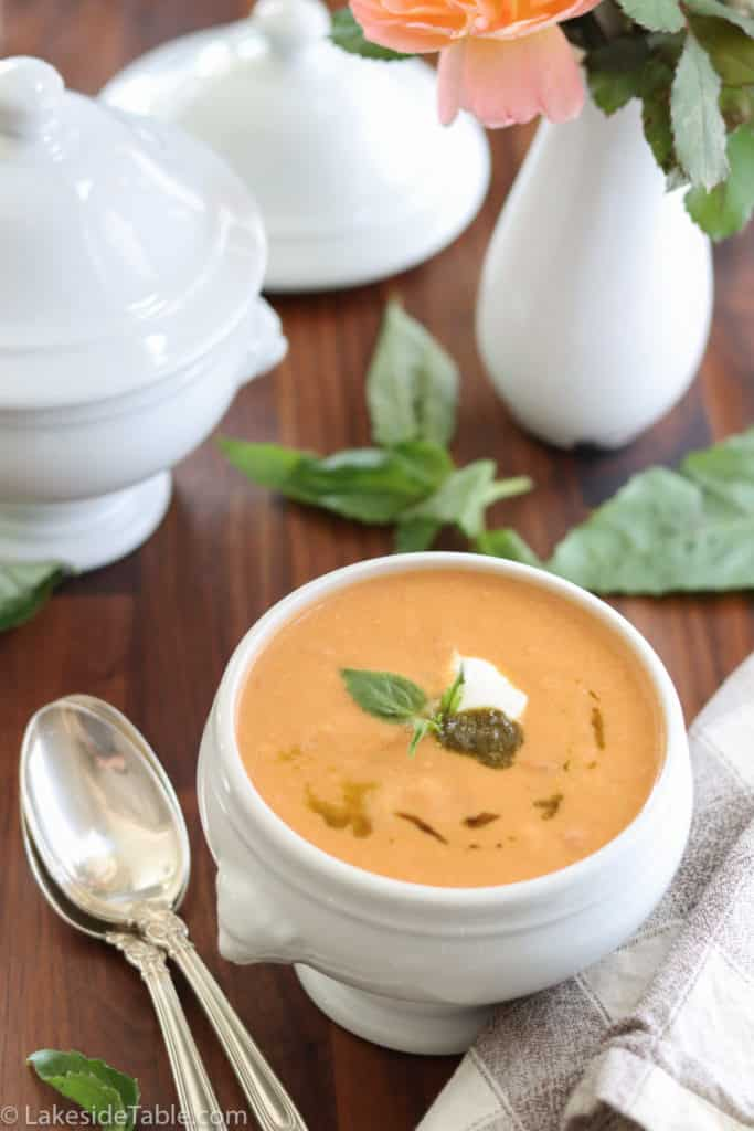 tomato soup with pesto, basil and sour cream in a white bowl