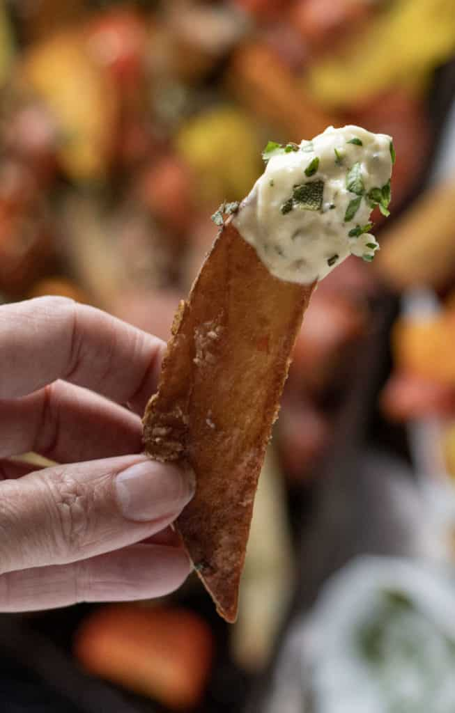 oven baked homemade french fry dipped in garlic aioli with fresh herbs