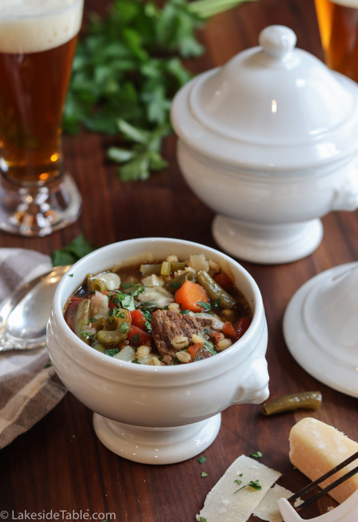 beef barley soup in a white footed bowl