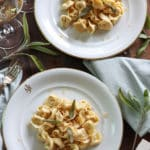 2 plates of finished tortellini pasta dripping with brown butter sauce topped with crispy sage leaves