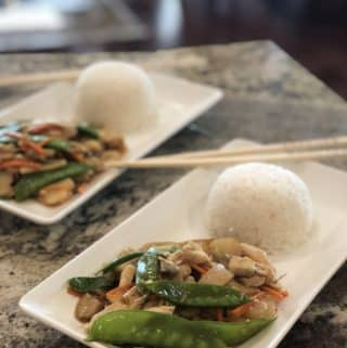 moo goo gai pan on a white plate with a ball of white rice and chop sticks